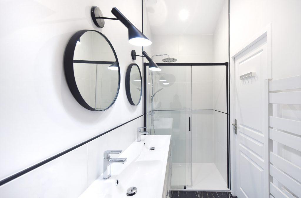 détails de la salle de bain : deux miroirs rond et lampe noire